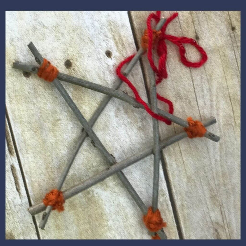 An epiphany craft that is a star made of wooden sticks and tied together with red and orange yarn