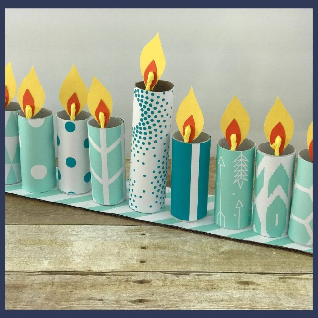 A menorah craft for Hanukkah that is made of cardboard and covered with decorative paper