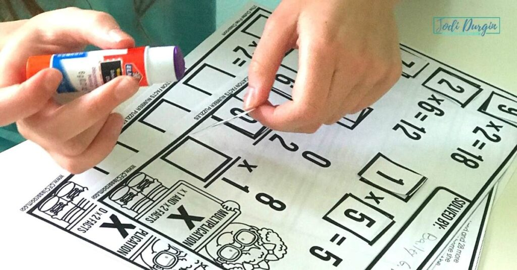 elementary student glueing number tile on math center activity puzzle